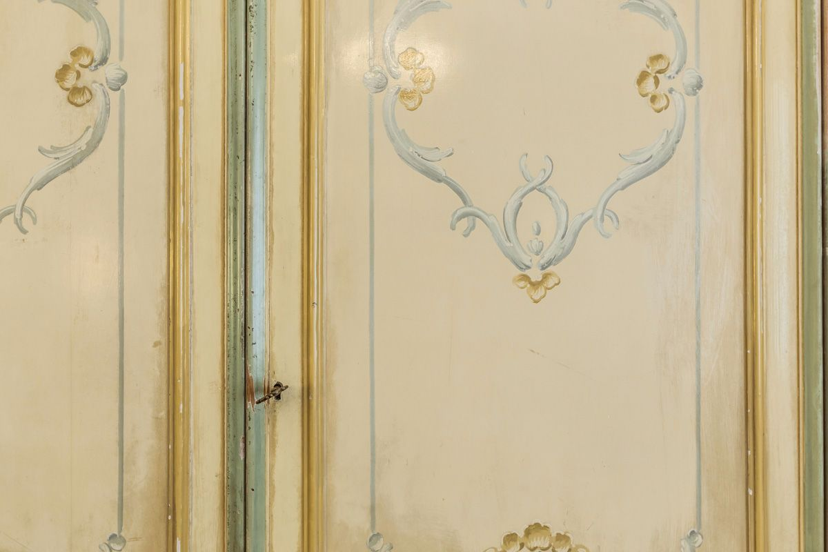 there is a large antique wardrobe with paintings