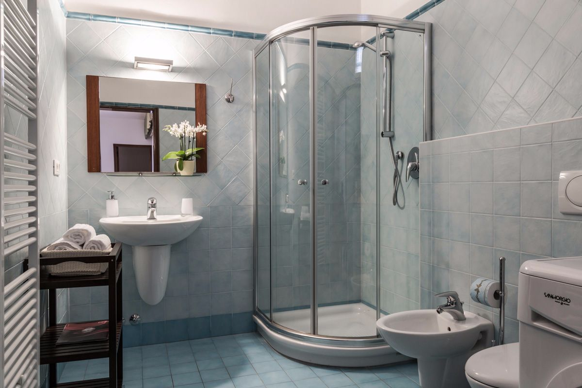 blue bathroom with large shower cabin and washing machine