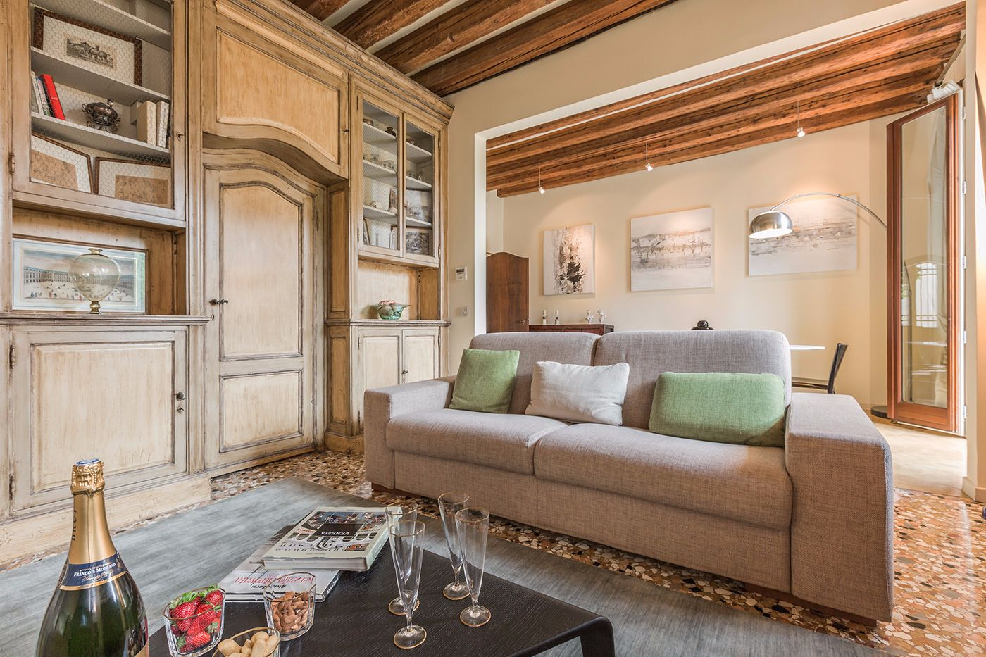 the welcoming living room features a rich boiserie and wooden beamed ceiling
