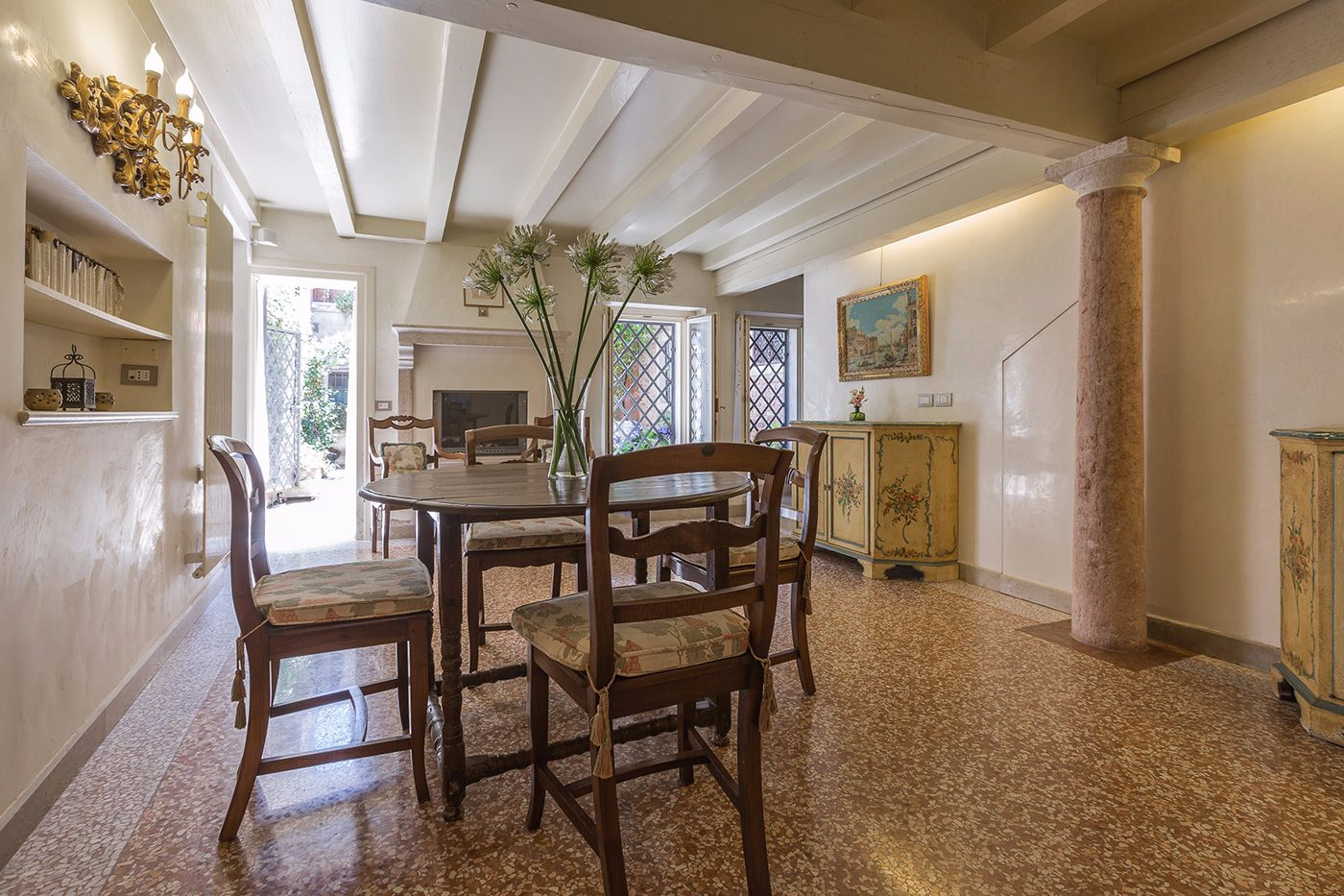 there is a spacious and elegant dining room that connects the entrance to the kitchen and courtyard