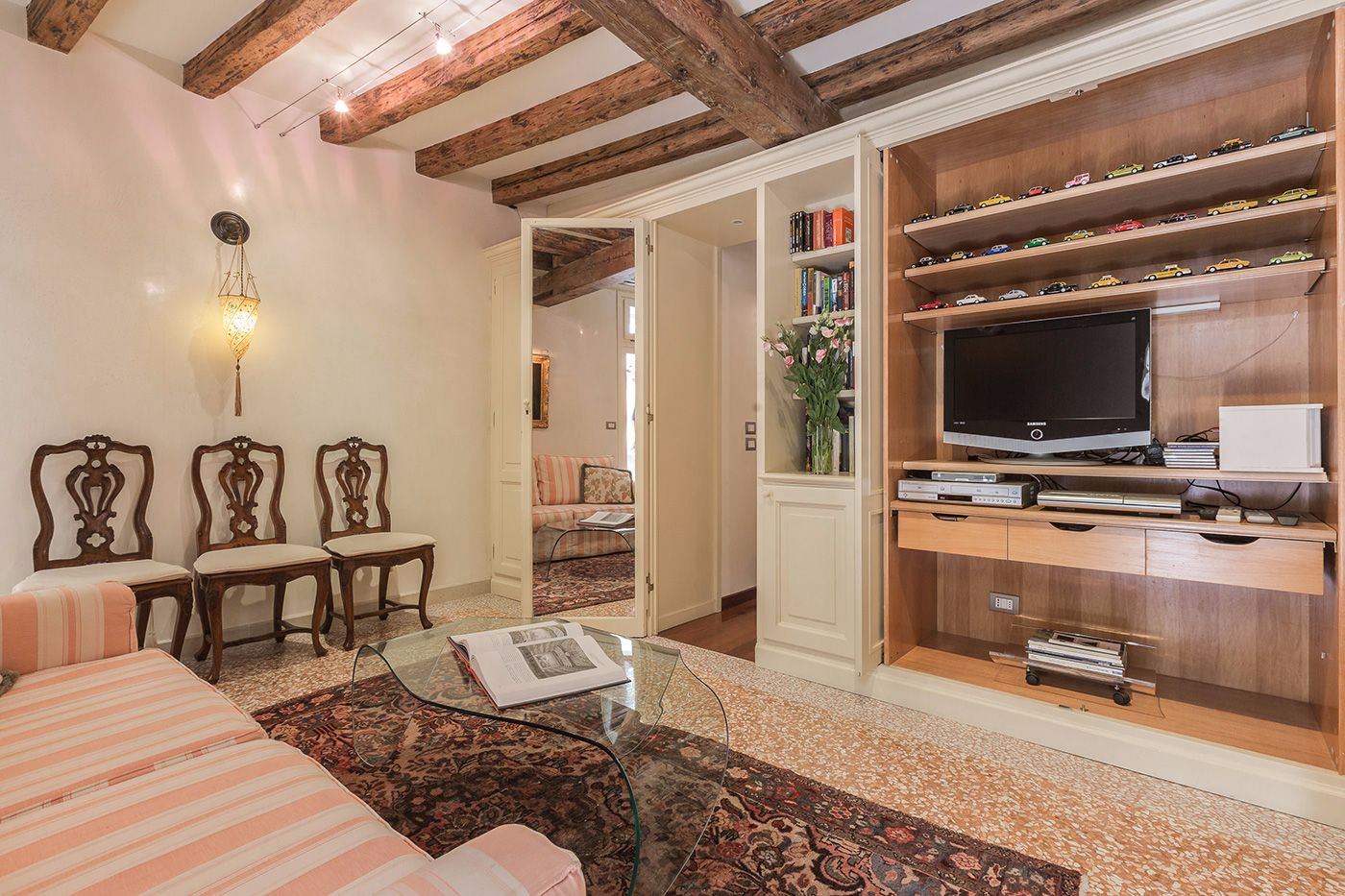 the living room is equipped with a large TV, DVD player, sound system and a library