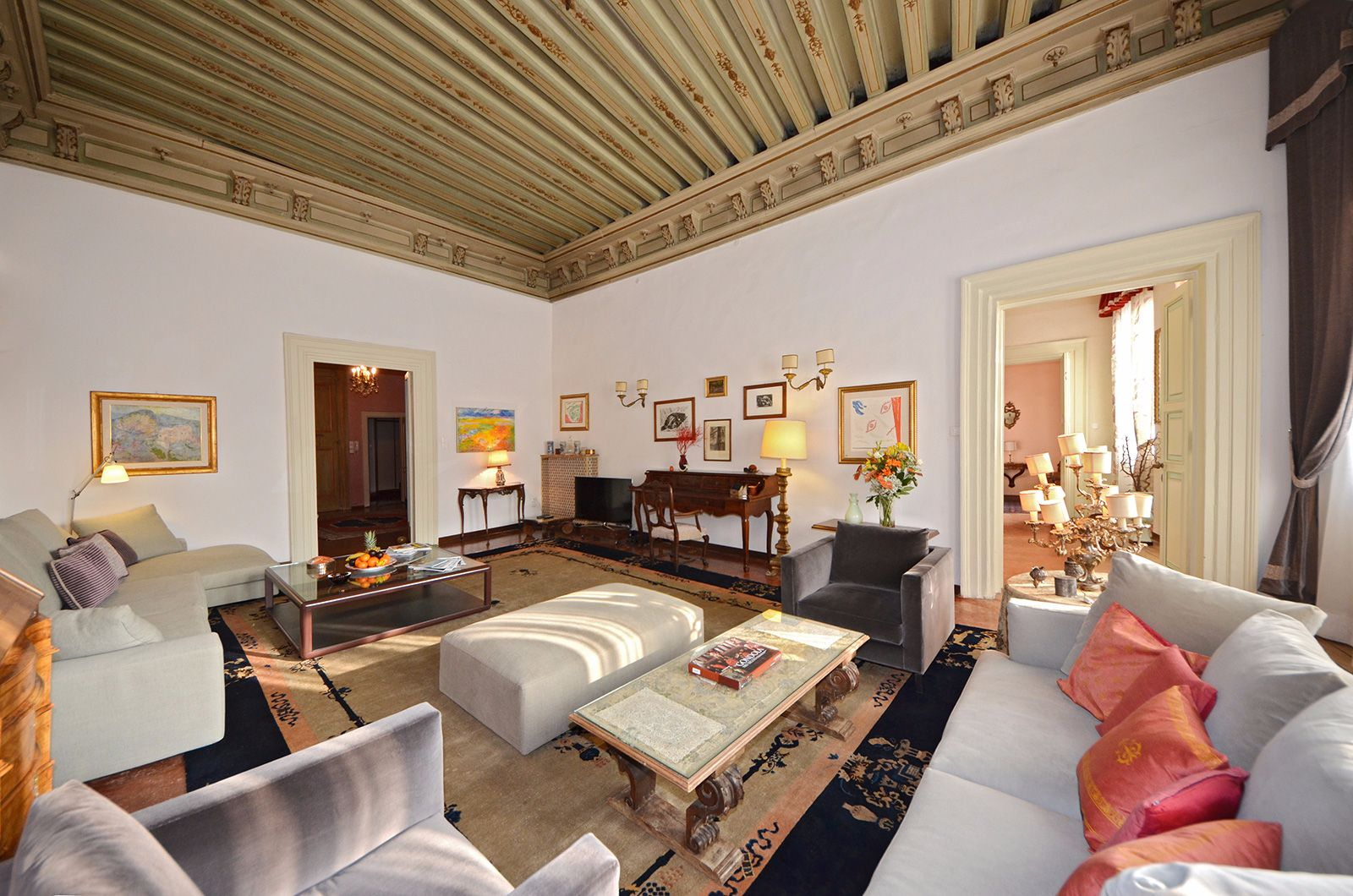 in the living room there are plenty of comfortable seats and antique furniture