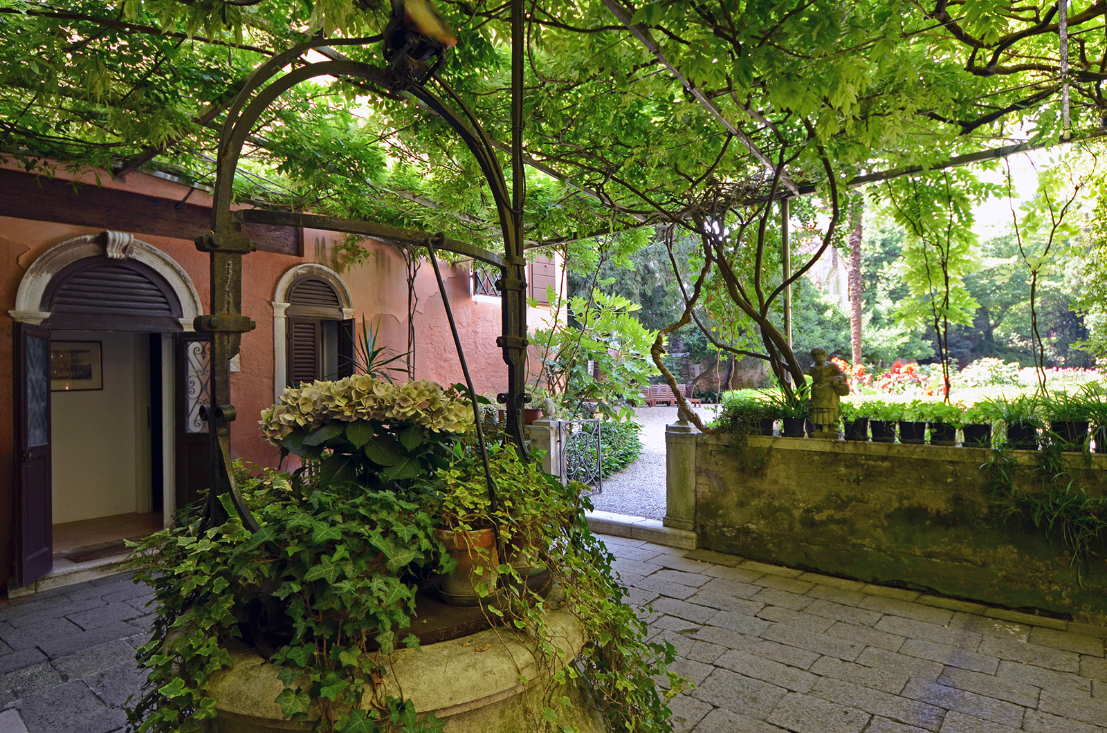 part of the courtyard is sheltered by a beautiful wisteria