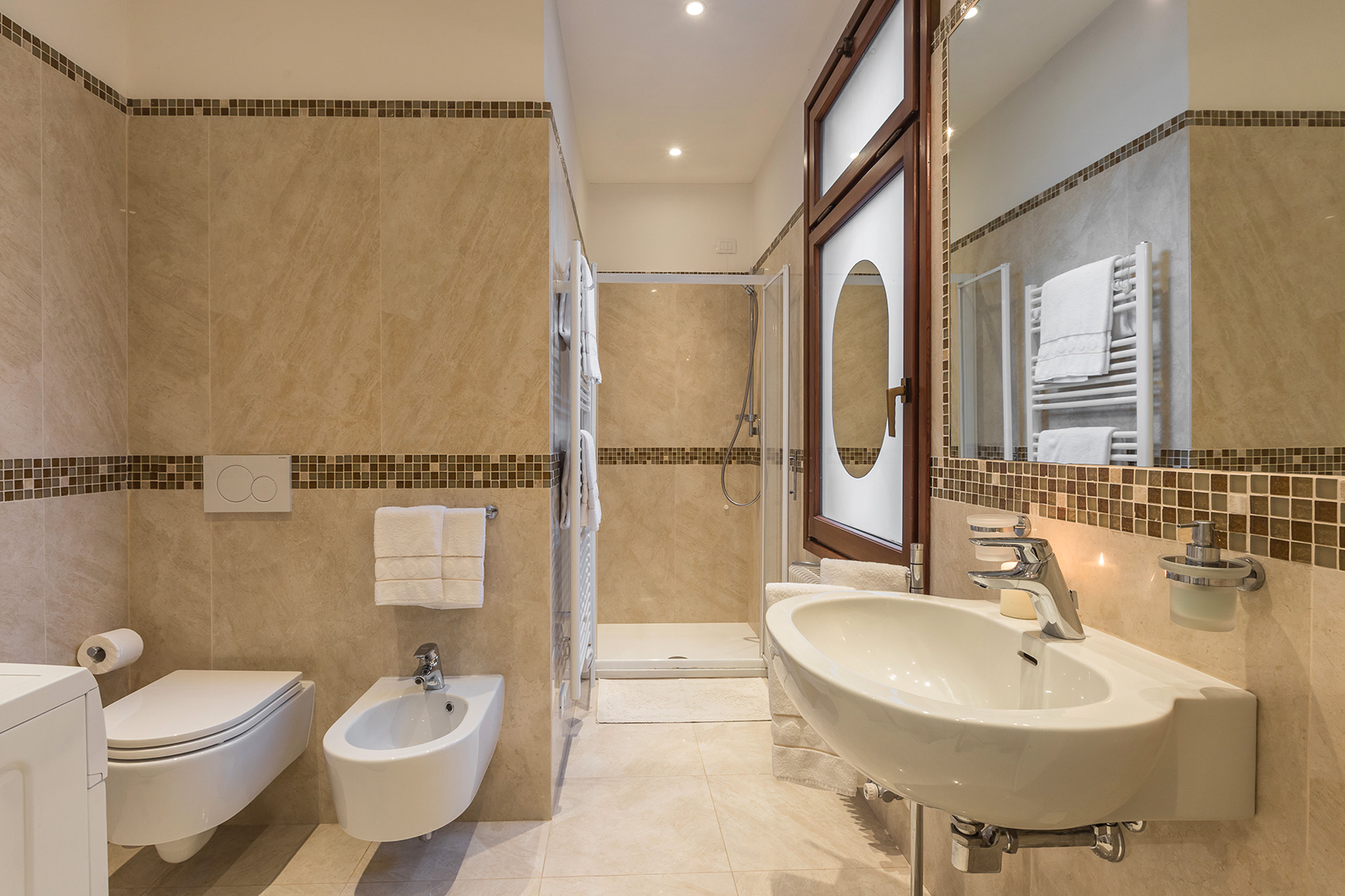 large en-suite bathroom made with marble and mosaic tiles