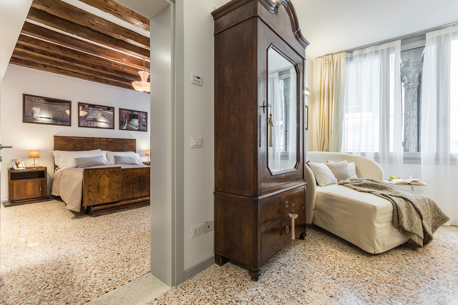 from the main bedroom you reach the central room where a small wardrobe and a day bed is located